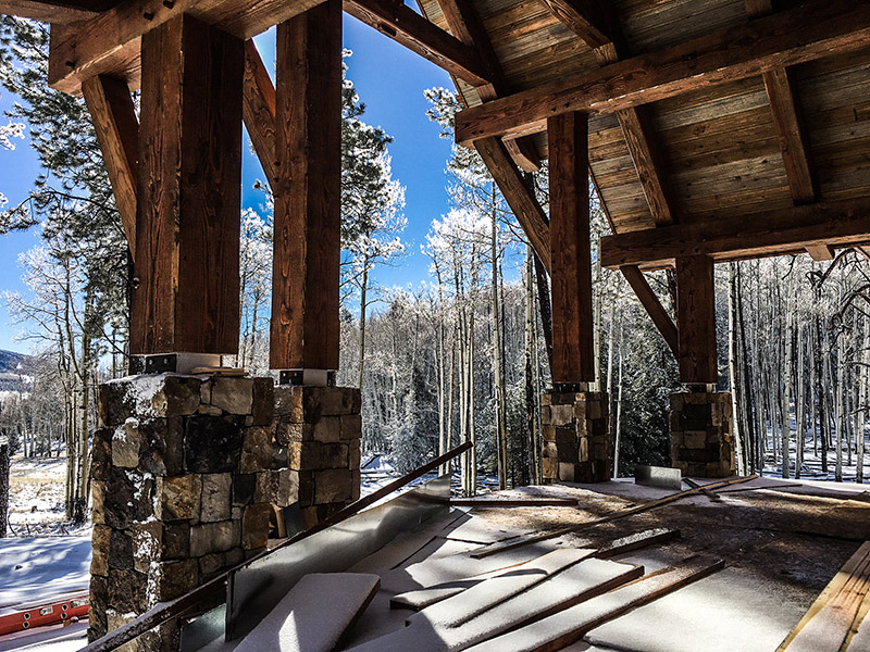 Porch posts covered in snow under timberbuilt roof