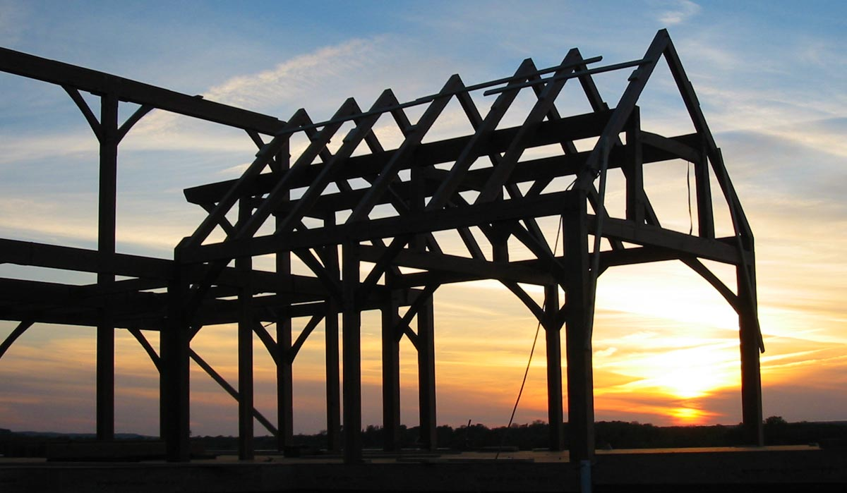 Silhouette of timber frame roof system with sunset in the background