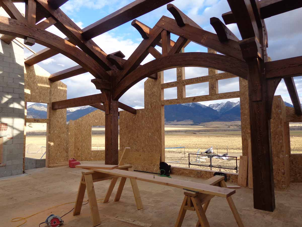 Timbers and structural insulated wall panels against the backdrop of a mountain range