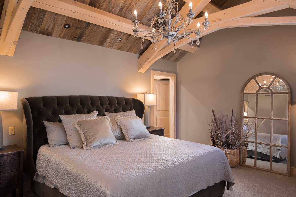Decorated bedroom with exposed timber frame roof system and tongue and groove paneling