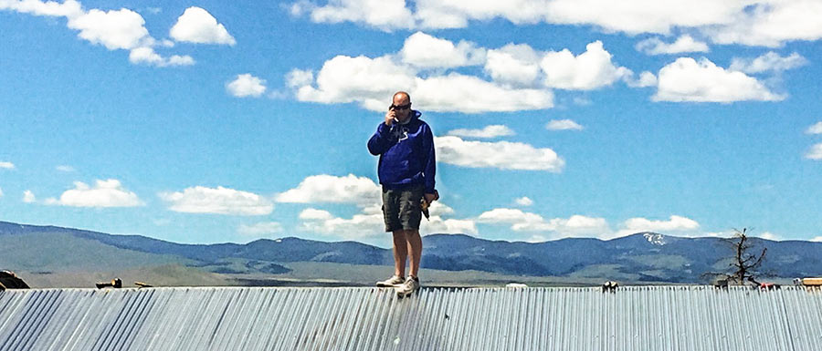 Timberbuilt operations manager, Adam Lincoln, on his phone, standing on a roof.
