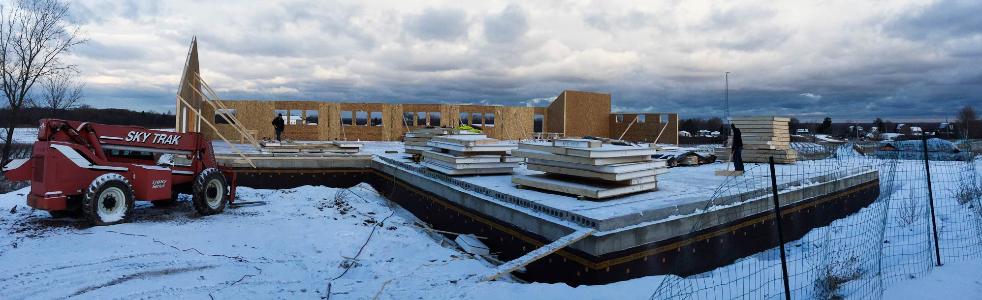 stacks of SIP panels on snowy foundation