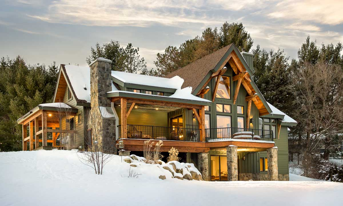 timber home design. Award winning timber frame home covered in snow with a huge porch and green  siding Timber Frame Home Designs Marshal Timberbuilt