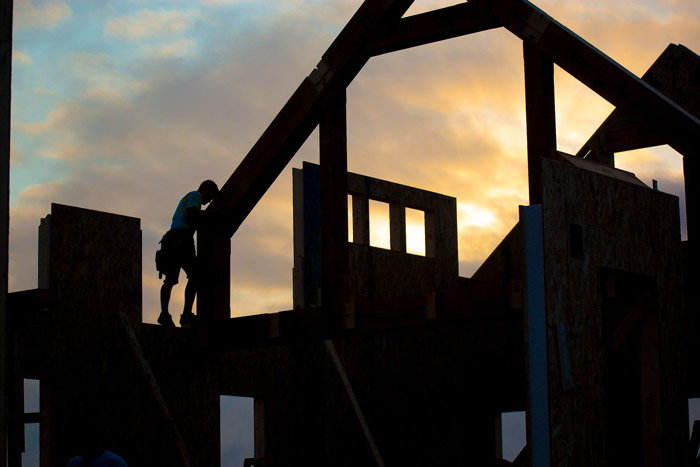 timber frame worker silhouetted against cloudy sunrise
