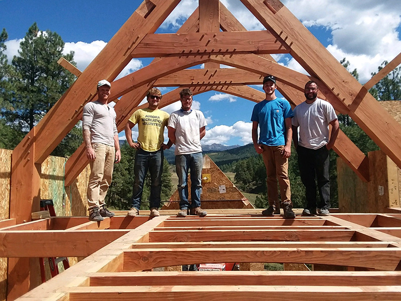timber framers standing on floor joists under sunny skies with extensive timber and peg roof structure over head