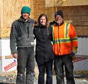 timber frame worker standing arm in arm with DIY clients