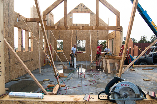timber home under construction with walls braced by 2x4s