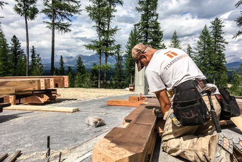 timber frame worker taking measurements of dark stained timber post with mountains in distance