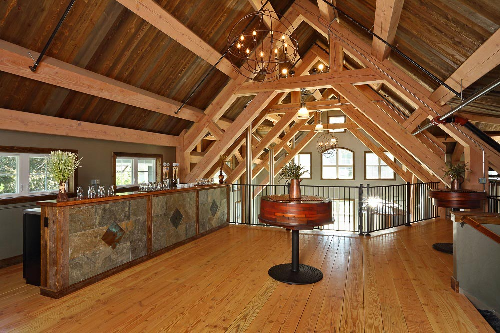 Second story loft of brewery featuring exposed white pine timber rafters, collar ties, and purlins