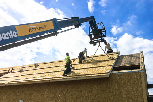 workers setting roof panels into place