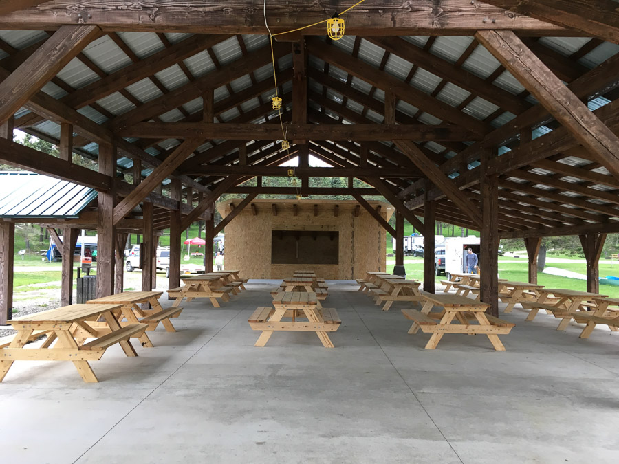 Underside of commercial timber frame with metal roof. Picnic tables beneath.