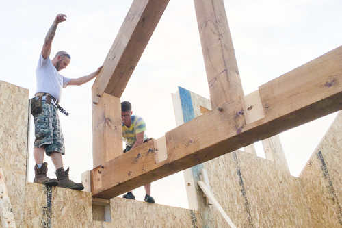 workers setting timbers into pockets of SIP walls
