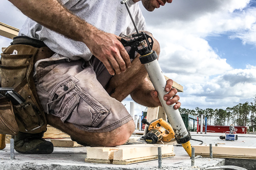 worker gluing wood plates to concrete foundation