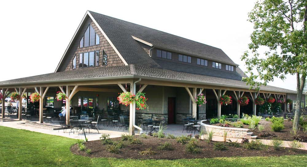 Brown shingled golf club house with sloped awning over a covered porch and timber posts