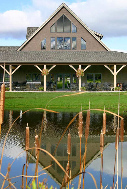 White pine timber posts and rafters support roof of golf club house which sits on a pond