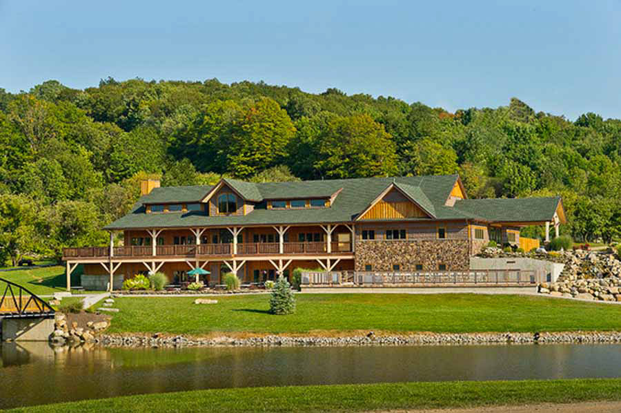 Three level, lake-front lodge with huge wrap-around porch with timber posts and landscaped grounds.