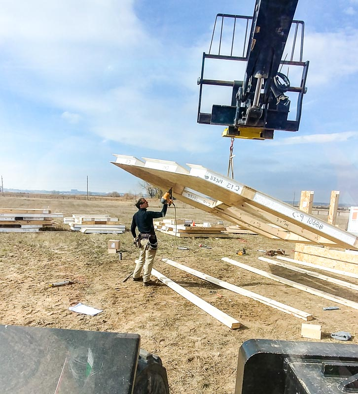 timber frame worker shooting SIP panels with nail gun