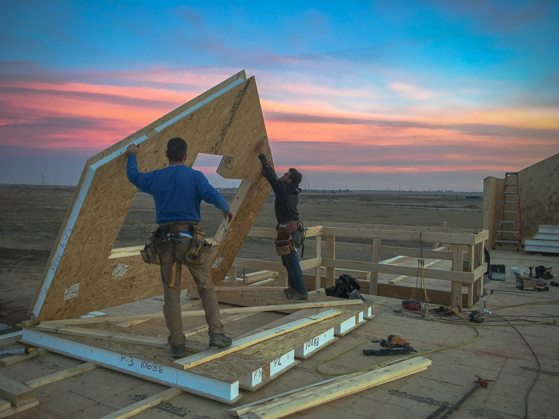 two timber framers standing up a wall made of structural insulated panels with a sunset behind them