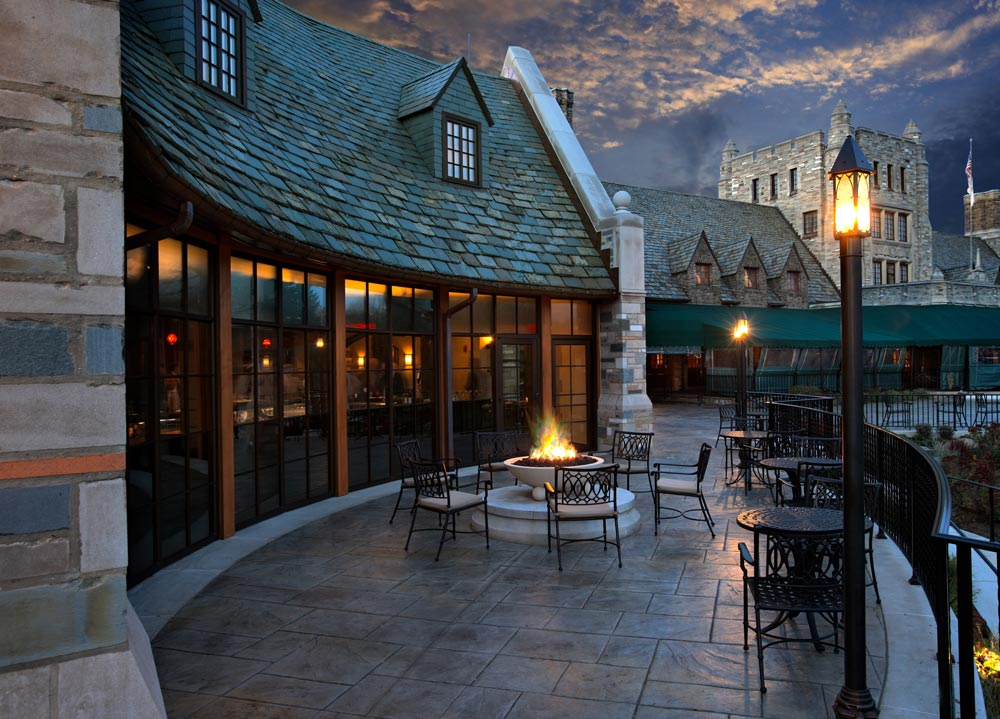 gothic country club with timber frame posts under a slate roof which faces dramatically lit patio