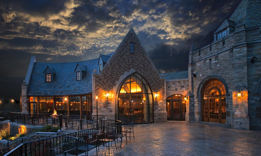 stone-walled private clubhouse at dusk with curved timber frame purlins facing the patio and gothic architecture