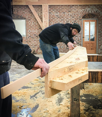 timber framer marks a curved cut line along a length of eastern white pine