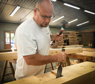 timber framer taps chisel into timber with mallet