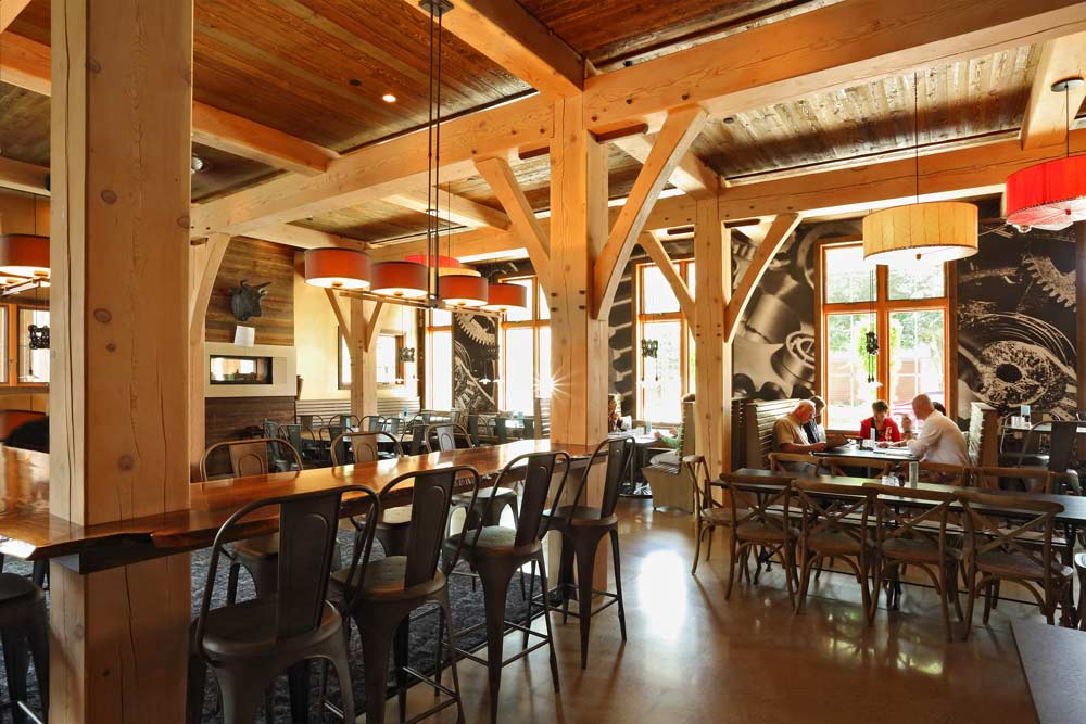 Dining room of an upscale restaurant with tables and chairs under a timber frame ceiling system