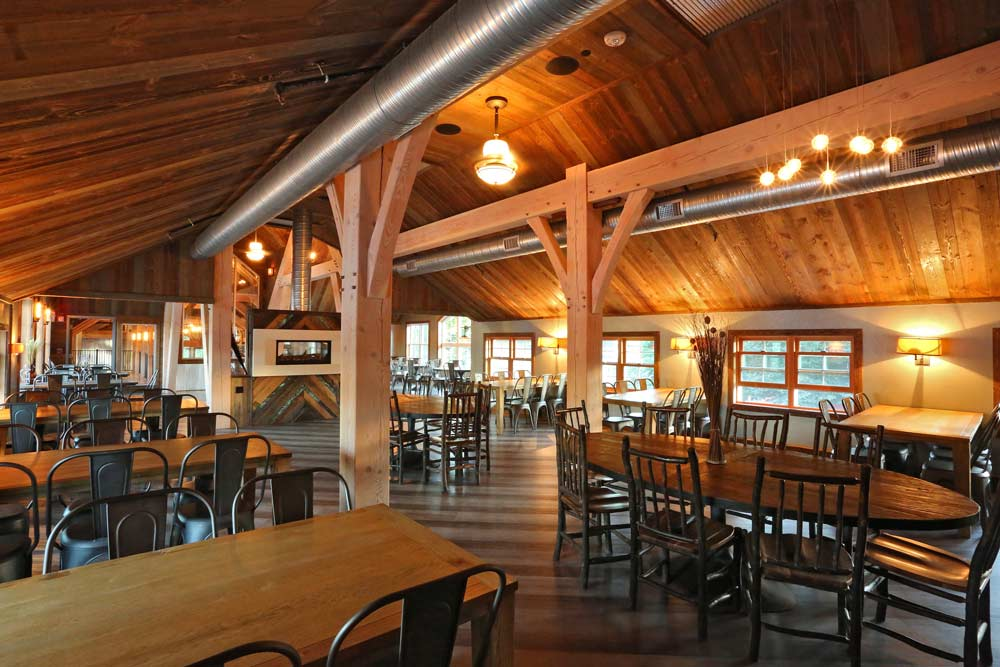 Timber framed restaurant with posts and braces and many tables and chairs